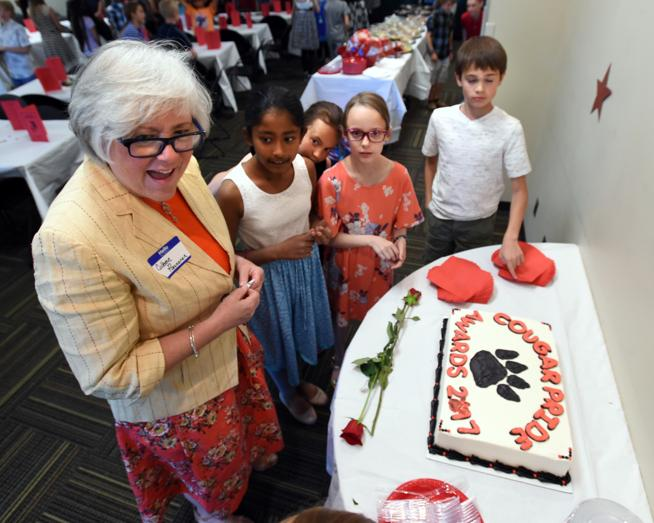 Retiring teacher Colleen Paananen looks over the cake with Tanvi Gawaande, left, Isabelle Blaustein, Eve Holburn and Noah Mayer on Wednesday at Lafayette